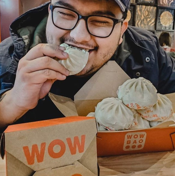 Guest biting into a bao and smiling