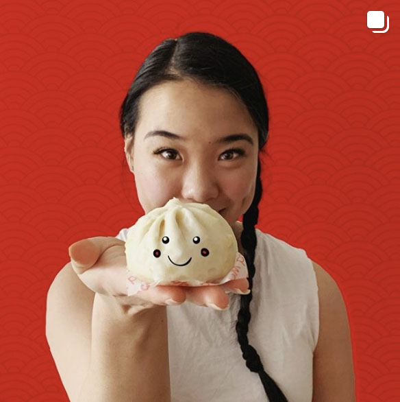 Girl holding a cute bao with a face drawn on it.