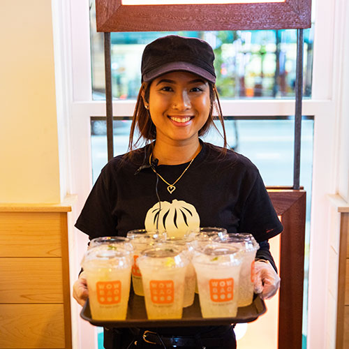 Employee smiling and holding a tray of drinks